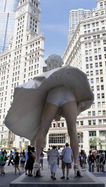 Curious spectators have their photo taken around Seward Johnson&#39;s 26-foot-tall sculpture of Marilyn Monroe, in her most famous wind-blown pose, on Michigan Ave. Friday, July 15, 2011 in Chicago. <span class=meta>(AP Photo&#47;Charles Rex Arbogast)</span>